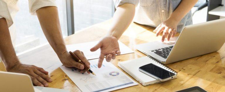 Pessoas em empresa analisando dados sobre uma mesa de trabalho